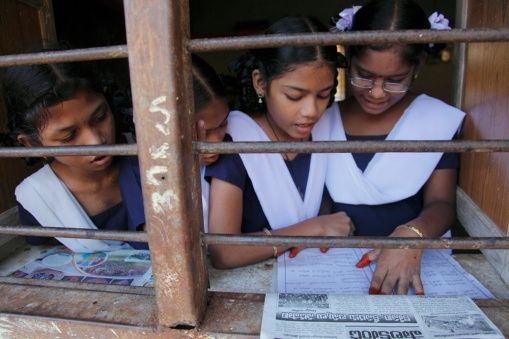 Students reading a textbook in their classroom at a school in Srikalulam, Andhra Pradesh.
